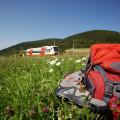 Roter Rucksack mit Wanderschuhen auf grüner Blumenwiese mit im Hintergrund fahrendem Ringzug